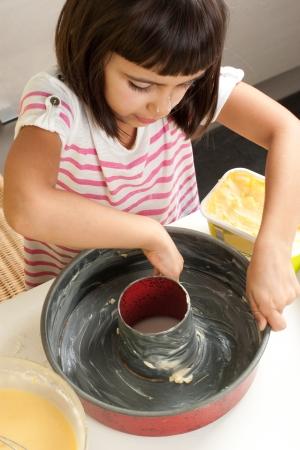 greasing: Ni�a feliz engrase un molde con la mano para hacer un pastel