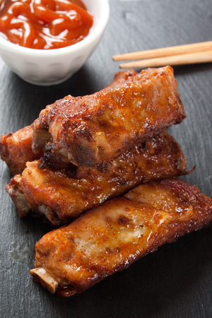 Close up of barbecue pork ribs in a slate plate with sauce and asian sticks photo