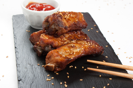 Close up of barbecue pork ribs with sesame in a slate plate with sauce and asian sticks over white background photo