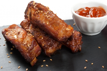 Close up of barbecue pork ribs with sesame in a slate plate with sauce  over white background photo