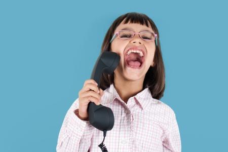 boca abierta: Niña divertida con gafas gritando en el teléfono retro con la boca abierta