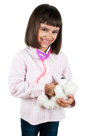 Funny little girl playing doctor with her teddy bear using a toy stethoscope photo