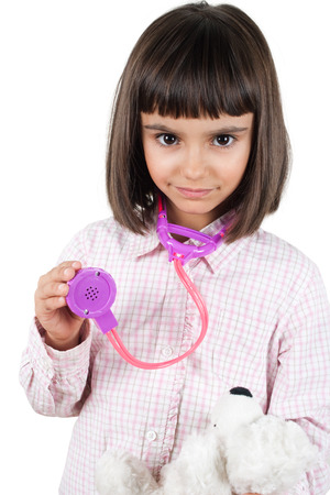Beautiful little girl playing doctor with her teddy bear using a toy stethoscope photo