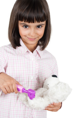 Beautiful little girl playing doctor with her teddy bear using a toy reflex hammer photo