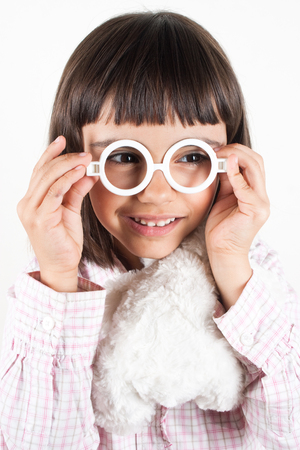 Cute little girl trying toy glasses photo