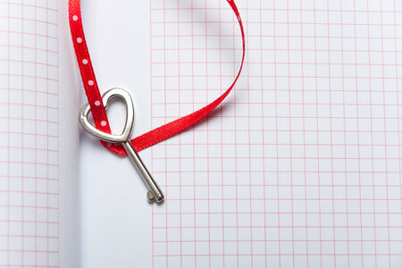 Heart shaped key tied with a red and dots ribbon on notebook . Copy space photo