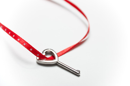 Heart shaped key tied with a red and dots ribbon on white  . Copy space