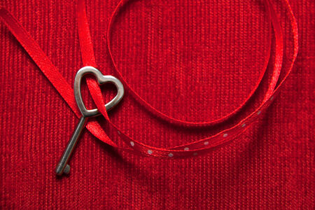 velvet background: Heart shaped key tied with a red and dots ribbon on red velvet . Copy space.