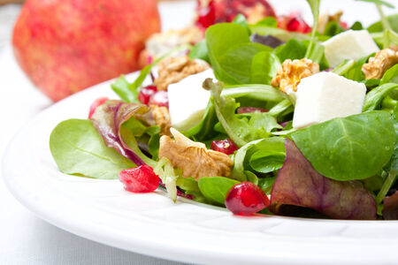 beautiful salad: Mix salad of baby leaf with fresh cheese, pomegranate and nuts  Pomegranate at the background