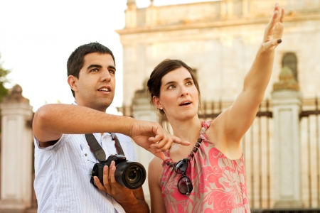 Attractive couple of tourists visiting the city and taking pictures of the monuments