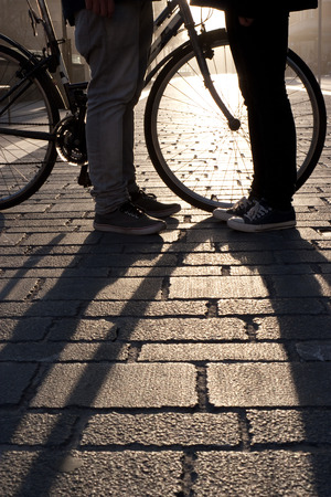 Legs of a young couple face to face with bicycle at sunset in the street photo