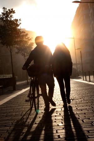 personnes qui marchent: Jeune couple marchant dans la rue avec un v�lo au coucher du soleil. Flare. Banque d'images