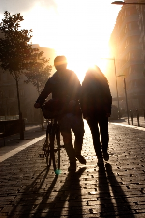 urban: Young couple walking down the street with a bicycle at sunset. Flare.