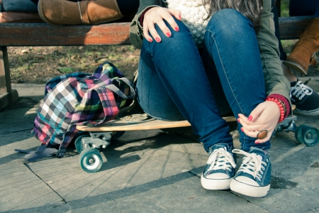 Legs of a girl sitting on a skateboard with his teenage friends in a park Foto de archivo