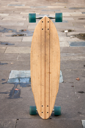 skate board: Skate board standing on the ground of the street after raining