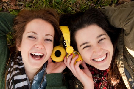 Two happy teenage girls lying on the grass sharing headphones to listen to music photo
