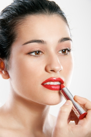 Beautiful exotic young woman applying red lipstick