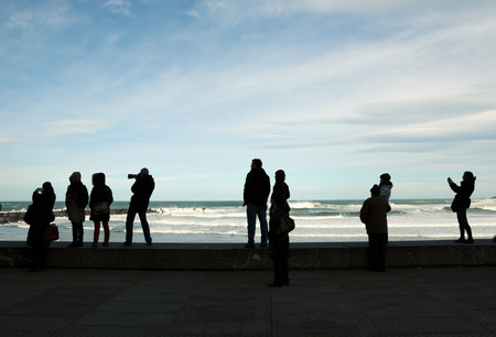 Silhouettes of people watching, photographing and recording with mobiles waves during stormy weather in winter