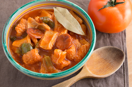 Rustic ceramic bowl of beef tripe with chorizo, tomato and pepper, a typical spanish food called  callos  photo