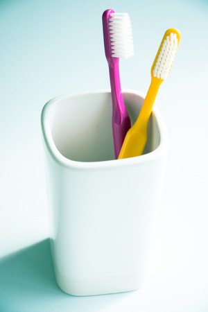 Two colorful toothbrushes in a mug photo