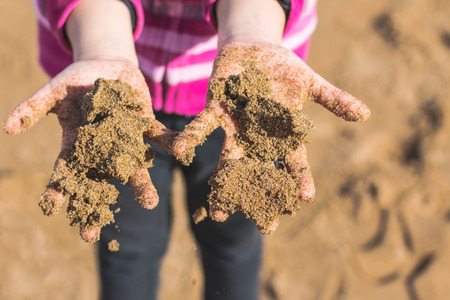 Hands of child full of wet sand on the beach  Soft focus