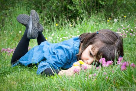 petite fille triste: Triste petite fille couchée dans l'herbe arrondi de fleurs au printemps Banque d'images