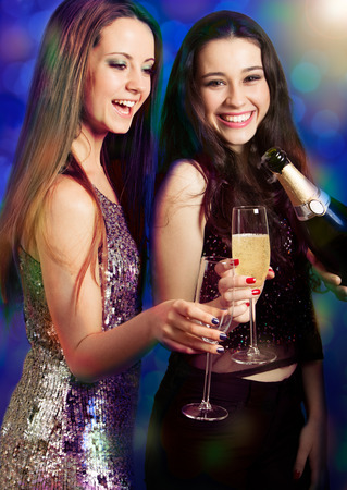 Two beautiful girls friends with champagne being served by a waiter at party or disco. Light effects. photo