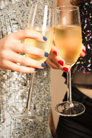 Hands of two girls toasting with champagne at party photo