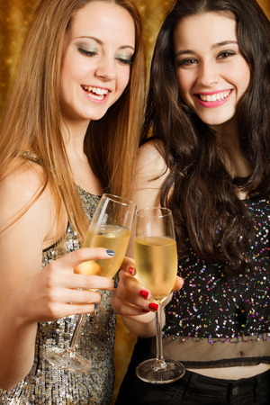 Two beautiful girl friends toasting with champagne at party photo