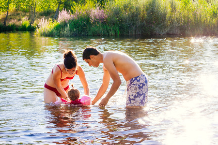 Atractive young couple playing with baby in the water of a river Stock Photo