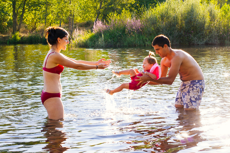 women bathing: Atractive young couple playing with baby in the water of a river Stock Photo