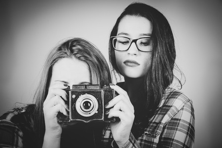 Serious hipster girls taking pictures with an old film camera.B&W retro filter effect added. photo