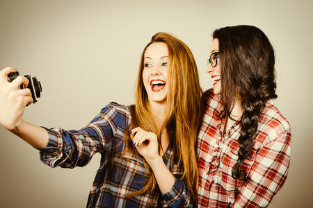 Funny hipster girls with plaid shirt and retro eye glasses making a selfie with an old film camera.Retro filter effect added.