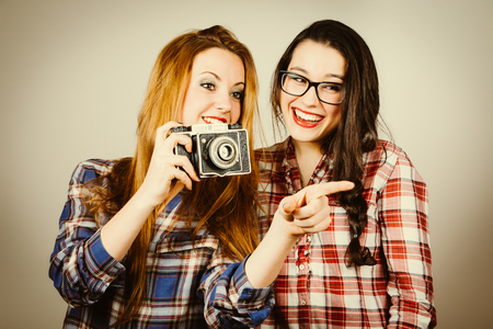 Funny hipster girls with plaid shirt and retro eye glasses taking pictures with an old film camera.Retro filter effect added. photo