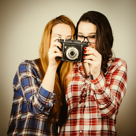 Funny hipster girls with plaid shirt and retro eye glasses learning to use an old film camera.Retro filter effect added. photo