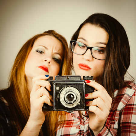 Serious hipster girls learning to use an old film camera.Retro filter effect added. photo