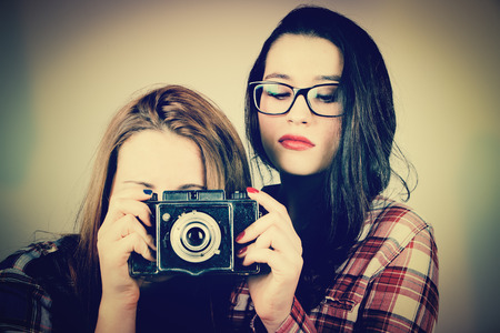Serious hipster girls taking pictures with an old film camera.Retro filter effect added. photo