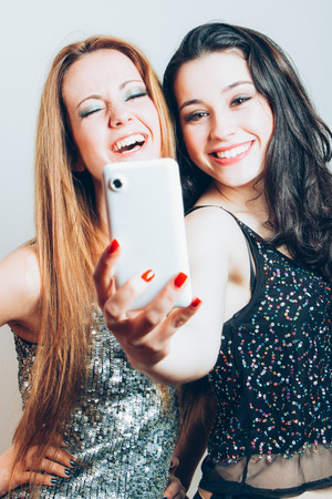 night out: Beautiful girls ready for a night out making a funny selfie with mobile