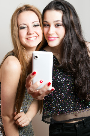 Beautiful girls ready for a night out making a funny selfie with mobile photo