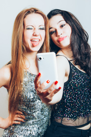 Beautiful girls ready for a night out making a funny selfie with mobile