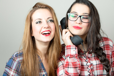 retro phone: Funny gossip girls with plais shirts on the phone.