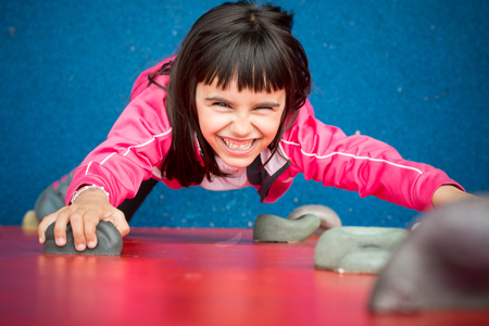 Pretty girl climbing a red wall in a playground photo
