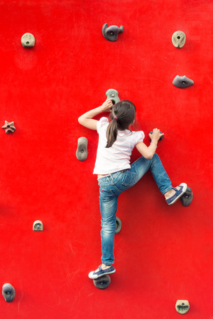 red jeans: Girl climbing a red wall in a playground
