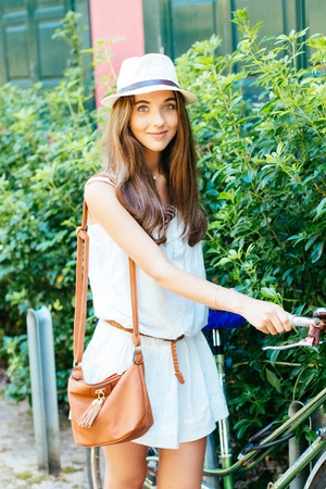 blue eyes: Beautiful and stylish girl wiyh hat parking her bicycle Stock Photo