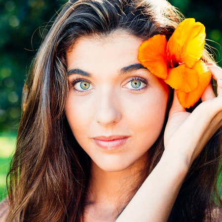 Portrait of a happy and beautiful young woman with flower in hair photo