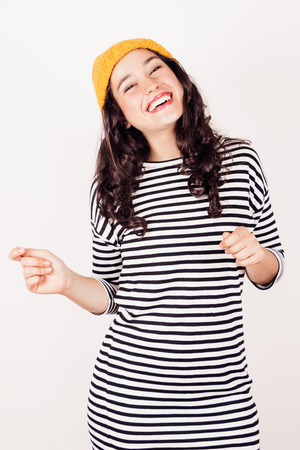 Smiling beautiful woman in striped dress and yellow wool cap dancing. Winter is coming and she is happy. photo