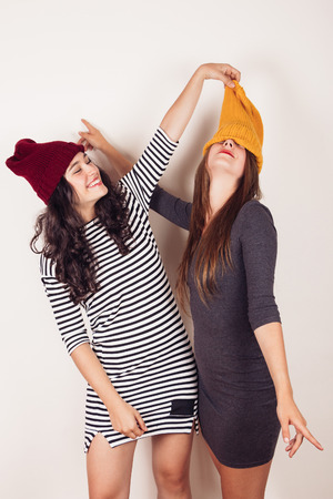 crazy girl: Funny and crazy girl friends with wool caps celebrating autumn or winter