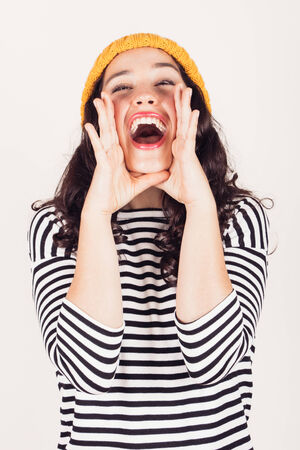 hands in mouth: Beautiful and funny girl with striped dress and yellow wool cap shouting hands next to her mouth. Focus on mouth