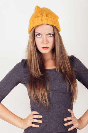 Sexy winter young woman in grey dress and yellow wool cap raising eyebrow photo