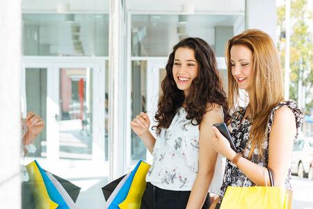 Beautiful shopping girls looking at a shop window
